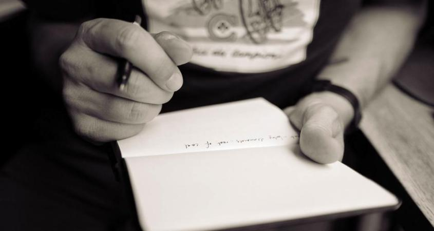 Image of a man holding a pen and notebook.