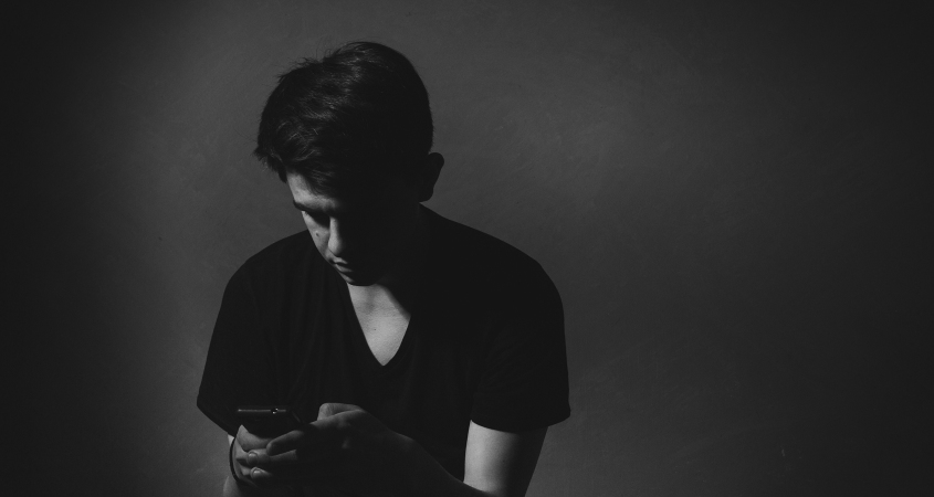 Image of a man texting on a smartphone